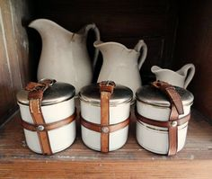 vintage enamelware canisters, 3 small tins with leather straps, white with gold striping from Germany. $85.00, via Etsy.