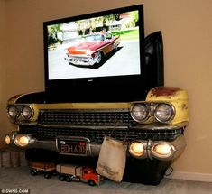 Porsche TV and Cadillac Sofa. Meet the petrolhead who decked out his living room with crashed cars Great man cave or game room idea. Old car front end for TV console.Great man cave or game room idea. Old car front end for TV console. Car Part Furniture, Automotive Furniture, Automotive Decor, Furniture Plans, System Furniture, Kids Furniture, 1959 Cadillac, Man Cave Diy, Man Cave Home Bar