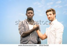 Afroamerican and caucasian men shaking hands in a modern handshake to show each other friendship and respect - Arm wrestling against racism on a blue sky - Shutterstock Premier