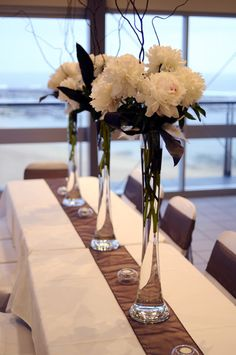 Eiffel tower vases with peonies and branches...simple and elegant - tall enough so people can still talk to each other from across the table!
