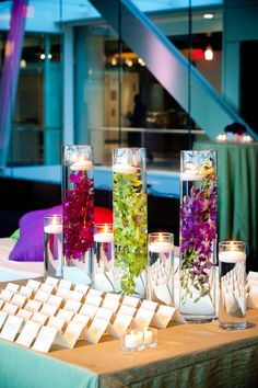 Place card table accented with colorful flowers and candles in cylinder vases - Amy Raab Photography