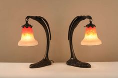 Pair of Art Deco Phoenix Lamps with Schneider Art Glass.  Resembling the legendary phoenix, these lamps feature a stunning modern design with signed Schneider glass shades
