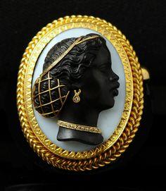 Broche pendentif en or ornée d'un camée ovale en onyx à deux couches représentant un profil de » négresse » en buste de profil à gauche. Le camée est « habillé » en or rehaussé de petits diamants taillés en rose, les cheveux coiffés en chignon sont ceinturés par un bandeau et retenus par une résille, un diamant en goutte est suspendu à l'oreille, un collier de diamants pare le cou du personnage. Magnifique sujet. Excellent état du camée avec un minuscule éclat à la base du cou. La résille…