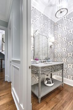 Boasting walls covered in Galbraith & Paul Lotus Wallpaper, this contemporary gray powder room features a stunning gray oak washstand fitted with a shelf and gray marble countertop finished with a round sink with a polished nickel faucet kit mounted beneath a beveled mirror illuminated by nickel sconces.