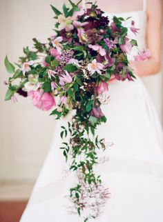 Deep green provides the perfectly grounded backdrop for an artistic array of purple and pink flowers. Via Style Me Pretty and Kayla Barker Fine Art Photography