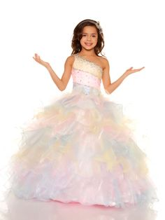 If you want your little girl to wear a pageant dress fancy and flashy, in this Sugar Mac Duggal 81679S she will look fantastic. A single shoulder strap extends from a diagonal neckline that tops off a three tone asymmetrical pleated bodice with beaded rows. The natural waist opens way to an organza iridescent skirt featuring fun ruffled layers. Available in Pink/Multi. We carry a great selection of stunning pageant accessories and shoes that she'll absolutely adore.