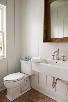 Vertical shiplap walls provide the perfect finishing touches to this welcoming cottage powder room fitted with a wall mounted sink finished with a polished nickel antique cross handle faucet fixed beneath a rustic vanity mirror with a shelf as floors are covered in red mini brick tiles.