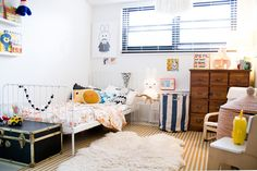 playful but neutral child's bedroom, white wrought iron bed , yellow and white striped rug