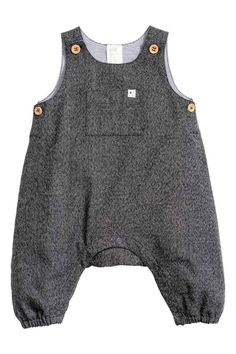 Dungaree romper suit: CONSCIOUS. Romper suit in a marled weave made from organic cotton with buttons on the shoulders and at the sides, a pocket on the tummy, press-studs at the crotch and elasticated hems. Lined at the top.