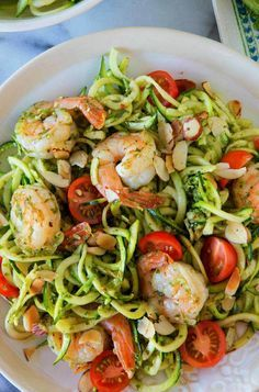 Use Veggie spiral for Zucchini-put in large bowl with coconut or olive oil...minced garlic and lemon juice...set aside. Put tomato...sliced almonds in 2 tbsp coconut oil and sautee....add shrimp. ..cover and sautee a couple minutes til done....in seperate skillet cover and sautee the zucchini. ..takes seconds...yummy