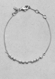 This subtle bracelet features small reptile-effect beads with silver finish.