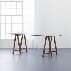 "Shop foundry 80"" trestle table.   Urban loft by way of a farmhouse feel.  Super-sleek glass tops lightly stained shesham wood rubbed with natural wax to bring out warm tones of the grain.  Brass support rods at the base add just the right amount of shine."