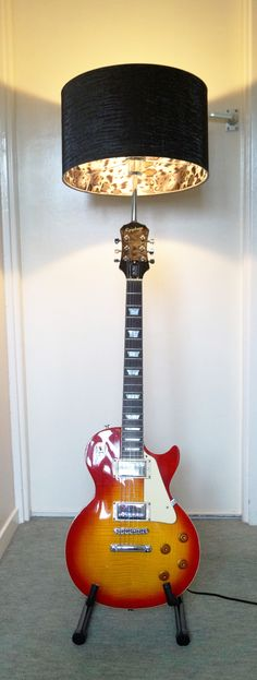 Up-cycled custom built classic sunburst Les Paul Epiphone guitar lamp. Animal print shade, on-off switch on guitar body set on a guitar stand. Available for sale.