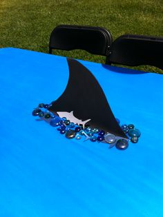 my shark table decor.   foam fin cut out,  cut hole in the table cloth and tape fin to table,  place rocks around the fin to cover edges.