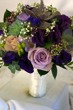 Purple and green bridal bouquet. Lilac roses, lisianthus, freesias, mint, succulents, eucalyptus