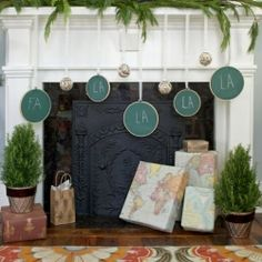 Mantle decorated for the holiday with shades of green and maps.