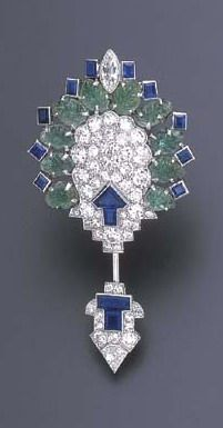 AN ART DECO EMERALD, SAPPHIRE AND DIAMOND JABOT BROOCH, BY CARTIER  Of geometric design, the shield-shaped plaque centering upon an old European-cut diamond panel, enhanced by a calibré-cut sapphire stylized arrowhead, extending a carved emerald demi-surround, of foliate motif, with a navette-shaped diamond and calibré-cut sapphire accents, to the detachable terminal, of similar design, mounted in platinum, circa 1925