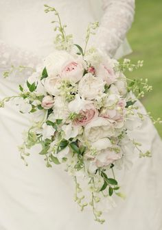A romantic teardrop bouquet of garden roses, sweetpeas and larkspur.