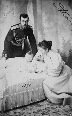 Nicholas II, Imperador da Rússia, Alexandra Feodorovna, Imperatriz da Rússia e Grã-duquesa Olga Nikolaevna. A bebê grã-duquesa Olga está sentada em um sofá olhando para a câmera. Alexandra Feodorovna está sentada à direita olhando para a filha. Nicholas, vestindo uniforme militar, está de pé atrás do sofá inclinado para a frente. A fotografia é assinada 'Nicky Alix Olga 1896'.