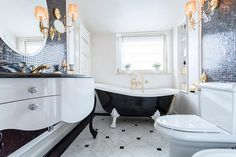 A small bathroom with beautiful black mosaic tile, a black and white clawfoot bathtub, and built in shelving near the tub.