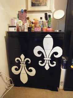 My latest project! I got the idea here:  http://uglythenpretty.blogspot.ca/2010/10/damask-dresser.html   An old particle board dresser, sanded and painted w/ 3 coats of black tremclad (I let paint sit for a week). I bought Fleur de Lis stencils here:   https://www.etsy.com/transaction/80517092  the seller made it according to my specs. I applied stencils w/ painters tape and painted inside white (3-4 coats) and then one coat of varnish. I'm in the market for thin b drawer pulls to blend in.