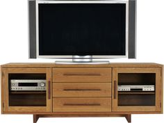 This Modern American TV-Media Stand is perfect for your living room. It is simple and elegant. Shown in natural cherry wood with black walnut accents. Customize this wood TV stand online.