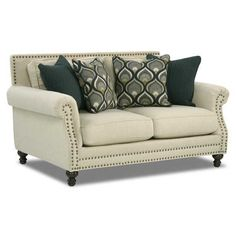 Add class to your home with the Spade Oatfield Loveseat from Corinthian Fine Furniture. Frames are constructed of sturdy hardwoods and plywoods with quality foam cushion core construction for seating comfort. This couch is covered in an oatmeal colored polyester fabric with eye catching accent pillows. The rolled arm is detailed with nail head accent trim.
