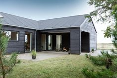 an elegant veranda with concrete flooring in beautiful black wooden house with grassy field