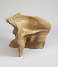 Irregular, contoured shape composed of thin layers of plywood, laser-cut, stacked, and laminated to form base, seat, arms/back, all of a piece.