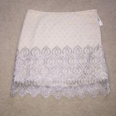 Free People Skirt NWT. STUNNING skirt by Free People. Ivory netting overlay with silver metallic detail. Zips on side. Length of lining measure 14 in and overlay measures 17 and 16 in at varying peaks. Free People Skirts Mini