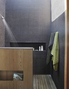 In the master-bath shower, the walls are clad in black porcelain tiles that soar up to a wall-to-wall skylight.