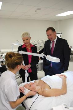 Charlotte performing a facial electrical treatment on Octaviana while speaking with Principal Catherine Wouters and Prime Minister John Key.