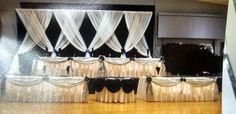Backdrop 1. Head table set up. Stage table for Bride, Groom, Maid of Honor and Best Man. Double tables on floor one for bridesmaids and other for groomsmen. Middle round table for the wedding cake.