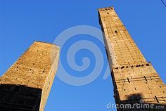 Photo made at the Asinelli and Garisenda in Bologna in Emilia Romagna (Italy). In the picture you see the two towers all'ungate toward the blue sky. Both towers are illuminated by the sun except the bottom in the shade.
