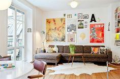 salon scandinave / joli coin canapé: peau de bête, table basse vintage et tableaux colorés