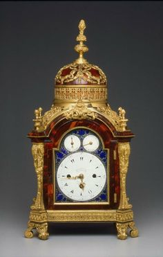 The rectangular tortoise-shell veneered clock case is canted at the corners and arches above the dial to support a dome surmounted by a tall baluster-shaped gilt-bronze finial. The case is supported on four double-scroll gilt-bronze feet.