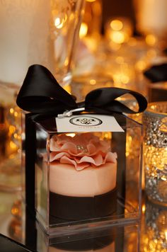 Clear lucite boxes adorned with the couple's logo hold pink and white mini cakes.