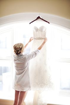 Get a picture wearing the grooms shirt while looking at your wedding dress