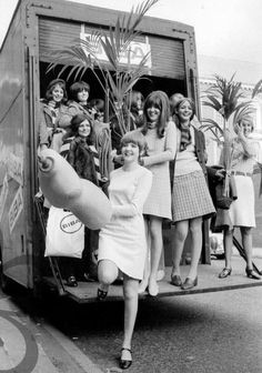 Kathy McGowan & Cilla Black, along with Biba staff carrying palm plants into the Biba store, 1960s