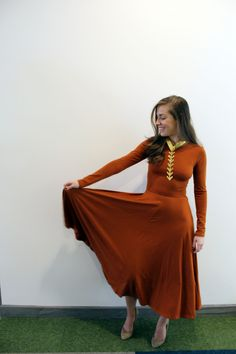 One of our Real Women Role Models wore this beautiful orange dress + statement necklace to her job in the fashion industry. Get more workwear inspiration at skirttheceiling.com!