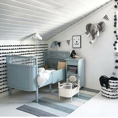 This kid's room is all sorts of wonderful!!! From the elephant plush head on the wall to the cool wall decals, this bedroom style is awesome. The bed looks like a convertible baby crib... I love those bed. They look super cool and they are very useful.