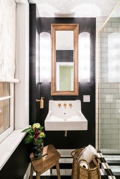 This elegant bathroom has a porcelain sink with gold fixtures, a gold-framed mirror, textured lighting, a black-and-white striped floor, wooden stool, woven basket, subway tile, and framed-in shower.