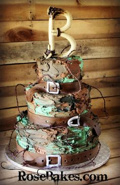 Buttercream Camouflage Groom's Cake. This rustic camouflage groom's cake appeals to so many men with barbed wire, deer antlers, camo and belts.