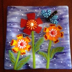 "9"" square whimsical flower plate by Kim Natwig.  Full fused base layers, then added 3-D features by soft fusing, and slumped.  Birthday present for my aunt."