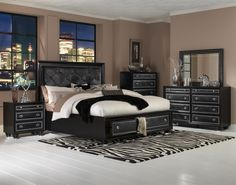 The Island Storage Bed offers a haute couture frame for the modern day fashion-follower. Crafted from hardwood solids with a silken black painted finish, both headboard and footboard have crocodile embossed PVC upholstered panels with shimmery, chrome-plated nail head trim. Side rails are double bolted for extra structural support, and rise as high as the footboard for a raised platform look. Rounded, tier-turned feet with chrome caps grace the footboard,