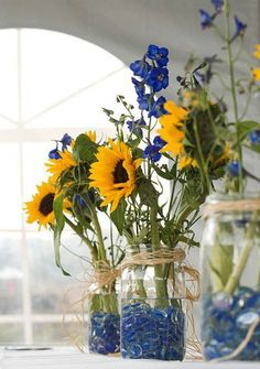 Mason jars con piedritas de vidrio en azul con margaritones y delphiniums azules para tus centros de mesa económicos y veraniegos y no olvidemos, originales.