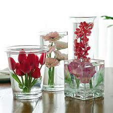 trio of vases, two taller with submerged flowers, shorter to have bouquet, with  3 votives for half the tables