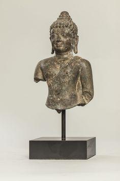 Buste de Bouddha vêtu de la robe monastique utarasanga lui couvrant l'épaule gauche lui moulant son corps juvénile replié en un pan plissé au dessus de la poitrine, son visage serein coiffé de larges bouclettes est surmonté de la protubérance crânienne ushnisha, terminé par un rasmi arrondi. Bronze à patine verte. Royaume de Chieng Sen. Thaïlande. 14ème à 15ème siècle. Ht 23 cm.