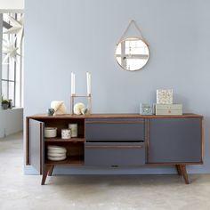 Dieses Sideboard stammt aus der Serie Niels, die für ihren skandinavischen Vintage Stil steht. Dieses Möbelstück erinnert mit dem eingesetzten Palisanderholz sowie geneigten Beinen an die 50er Jahre. Hinter zwei Türen befindet sich jeweils ein Regal und die zwei Schubladen liegen auf Holzschienen auf und bieten Stauraum für Geschirr, Servietten, Untersetzer und vieles mehr. Dieses Sideboard besticht mit seinem Design, das schlichte Eleganz ausdr&am...