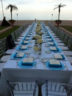 Long wedding reception table sits oceanfront at Acqualina Resort & Spa on the Beach.
